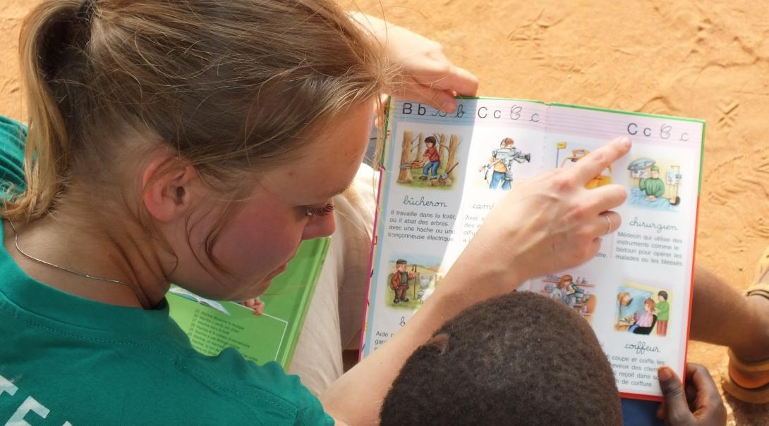 A child practices reading aloud at a care centre with a volunteering doing a Childcare Project in Africa.